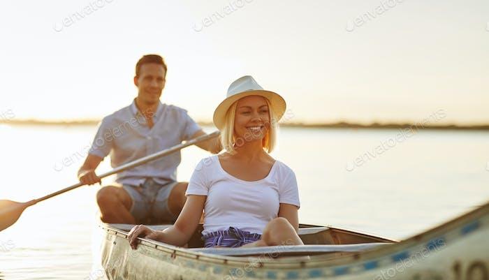 Lächelnd junges Paar genießen einen sonnigen Tag Kanufahren zusammen
