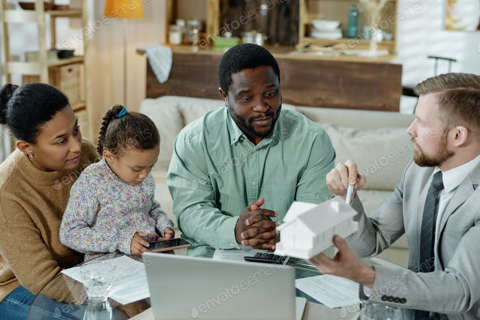 Man consulting young ethnic family on mortgage