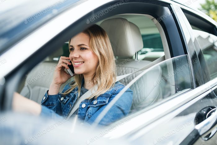 Young woman driver with smartphone sitting in car, making phone call.