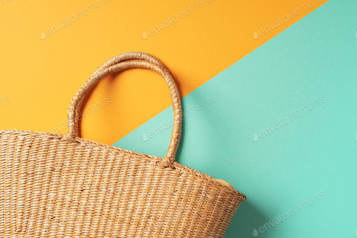 Women's straw bag on trendy yellow and green background. Top view. Copy space. Summer travel