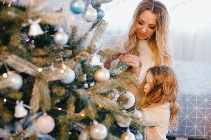 mother and daughter decorating the tree