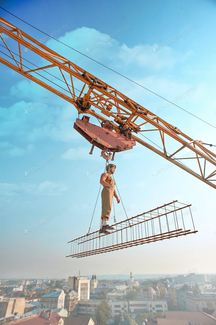 Crane holding construction with man over city