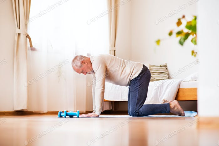 Senior Mann macht Übung zu Hause.
