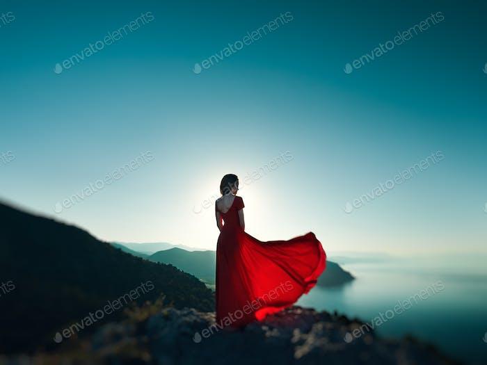 Junge schöne Frau in rotem Kleid Blick auf Berge Meer