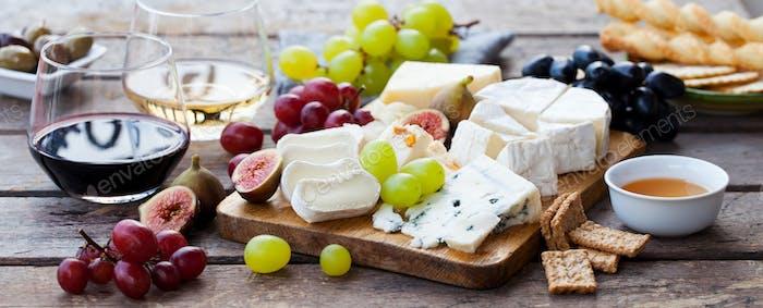 Käse- und Obstsortiment auf Schneidebrett mit rotem, weißem Wein auf Holzhintergrund.