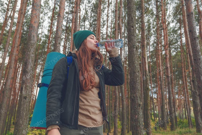 Hiker girl enjoying water. Happy woman tourist with backpack drinking water from bottle in nature