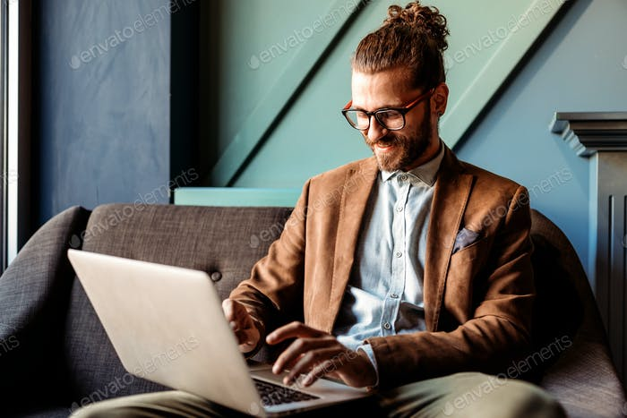 Happy successful businessman working with laptop at office