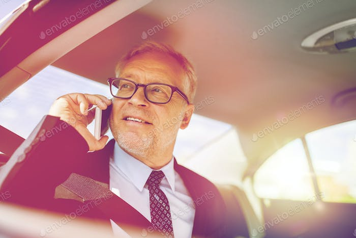 senior businessman calling on smartphone in car