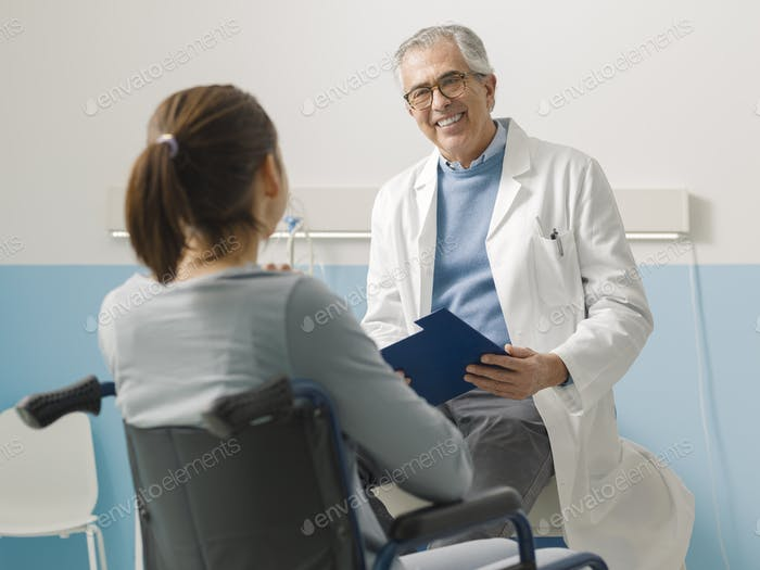 Doctor visiting a paraplegic patient at the hospital