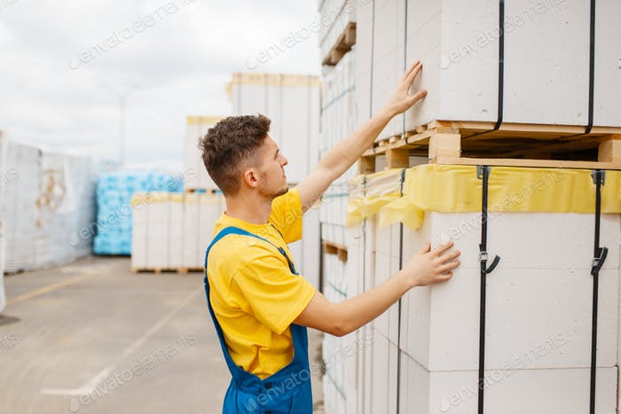Male builder at the pallets of insulation material