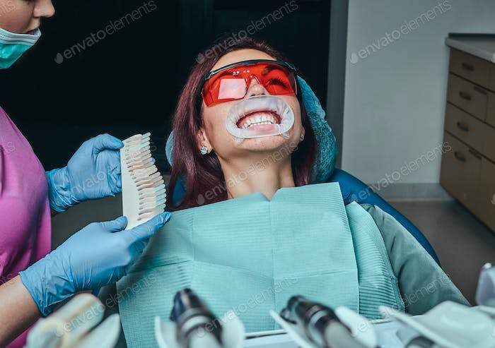 A woman dentist checks the level of teeth whitening with a dentist's color in the dentist office.