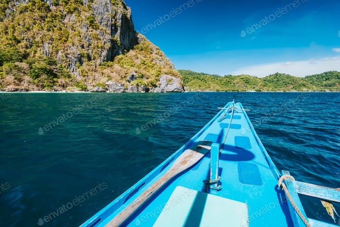 El Nido, Philippines. Island hopping Tour boat hover over open strait between exotic karst limestone