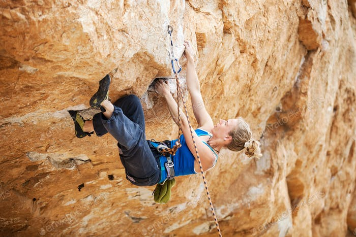 Rock climber struggling to make next movement up