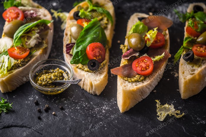 Slices of ciabatta with olives , tomatoes and basil on the black stone table