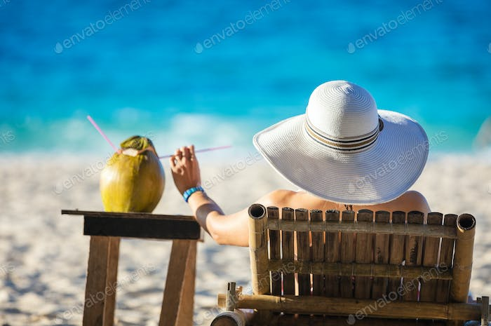Young woman sunbathing and drinking coconut juice on the beach