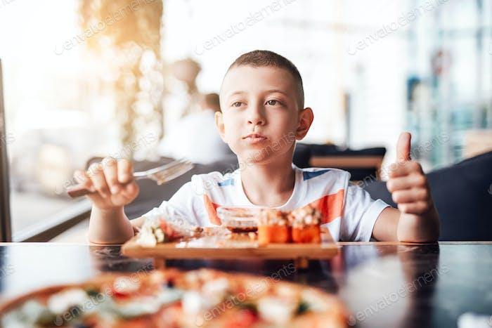 Boy enjoys eating sushi rolls in outdoor cafe