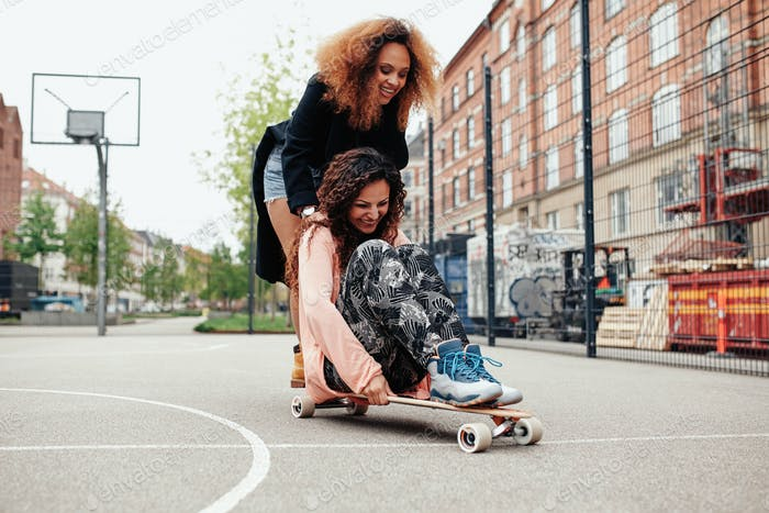 Two happy women having fun skating