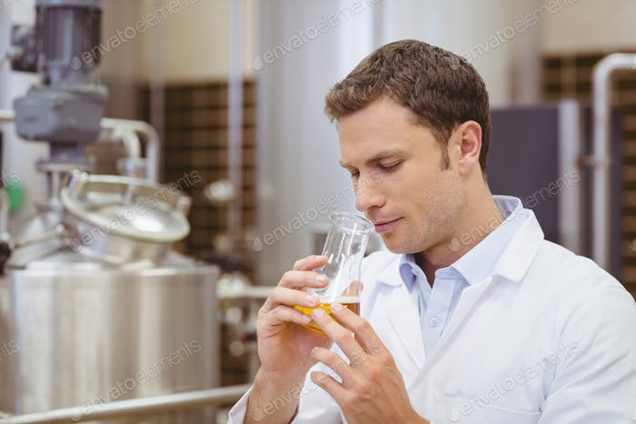 Focused brewer smelling beaker with beer in the factory