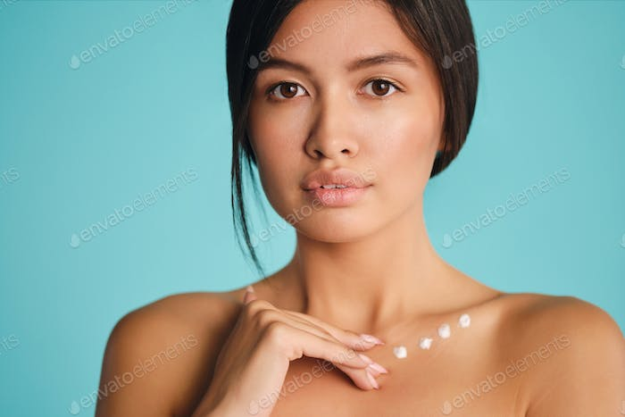 Charming Asian brunette girl with points of cream on clavicle intently looking in camera