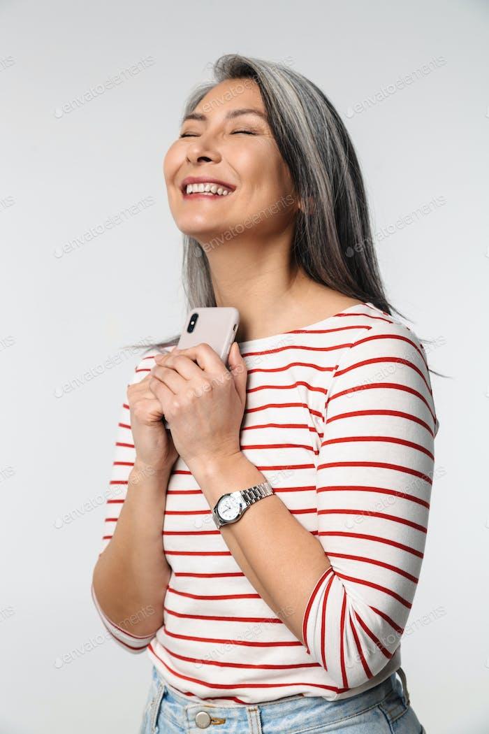 Bild von Erwachsenen reife glückliche Frau mit langen weißen Haaren hält Handy
