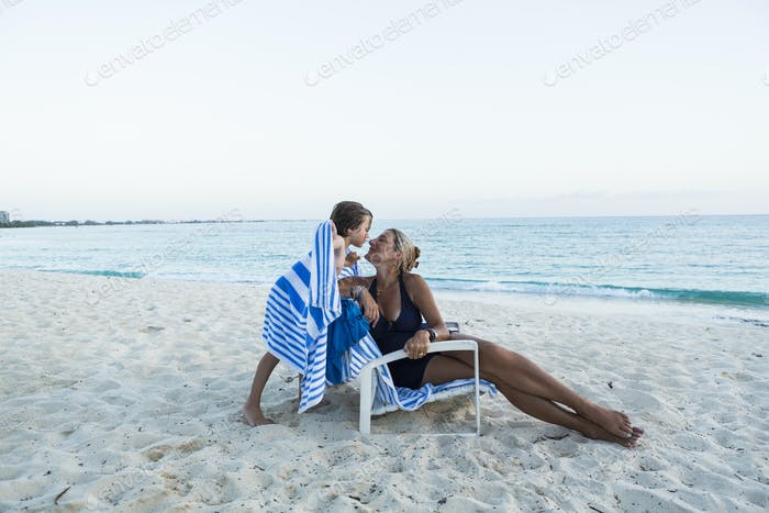 mother and her 5 year old son kissing on the beach