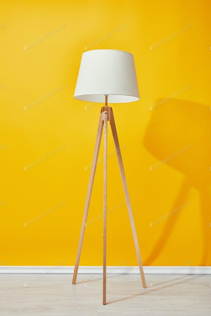 Minimalistic floor lamp near bright yellow wall
