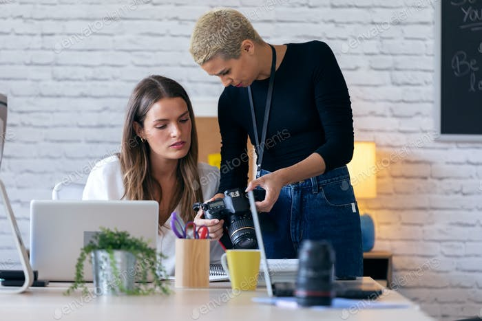 Modern entrepreneur women reviewing last photographs in the camera for they next work in the office.