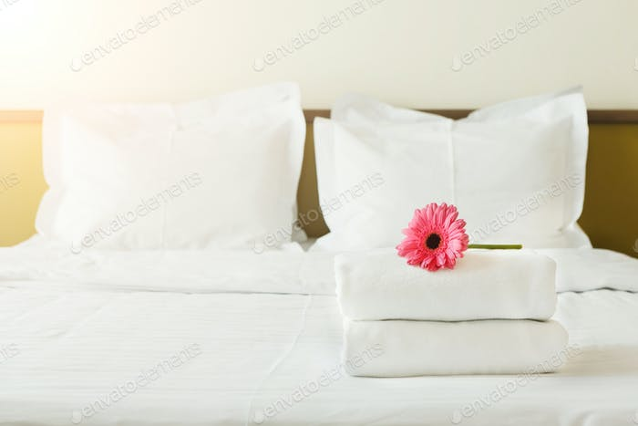 Stack of towels and flower on bed in hotel room