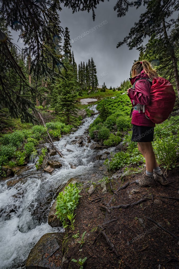 Hiking Colorado Girl Backpacker looks at cascading creek near la