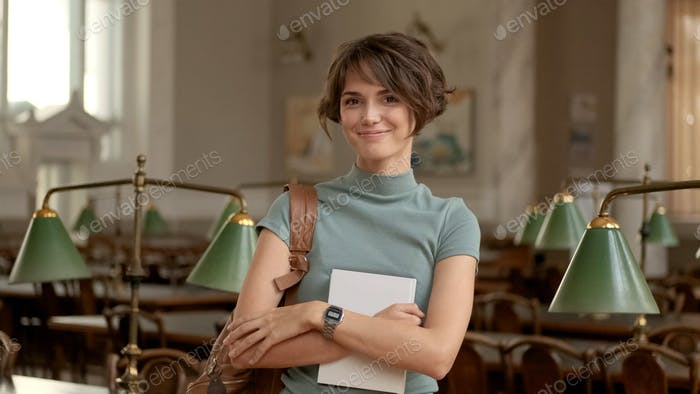 Beautiful student girl happily looking in camera holding backpack and textbook in college library