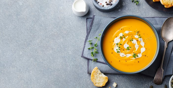 Pumpkin, carrot cream soup in a bowl. Grey background. Top view. Copy space.