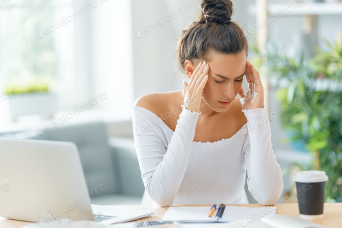 Young woman studying and having a head ache