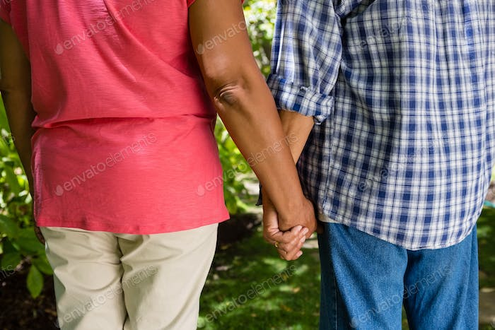 Mid-section of senior couple holding hands