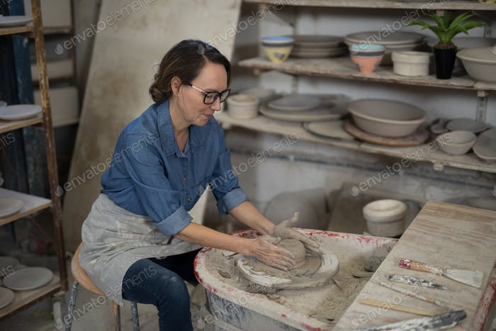 Female potter molding a clay