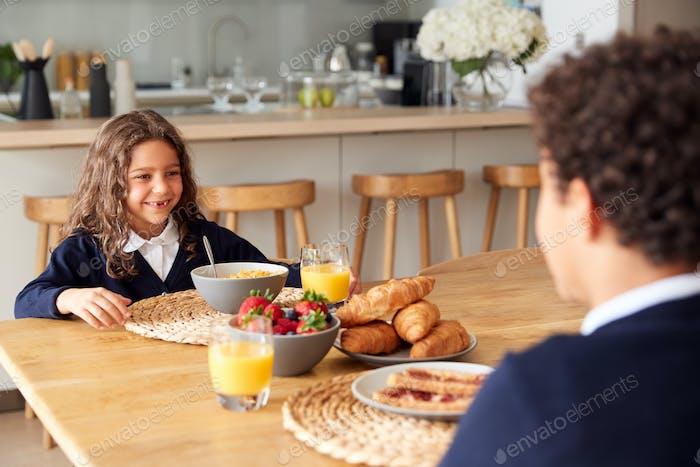 Children Wearing Uniform In Kitchen Eating Breakfast Before Going To School