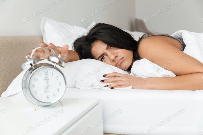 Bild der unzufriedenen Frau 20er Jahre im Bett auf Kissen liegen, und drehen