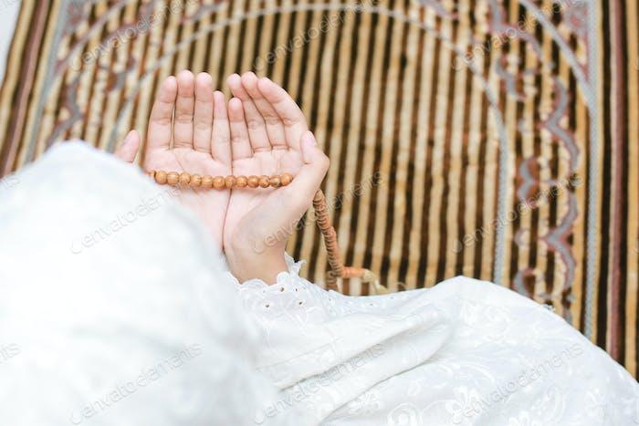 Mano de mujer musulmana rezando en la alfombra de oración