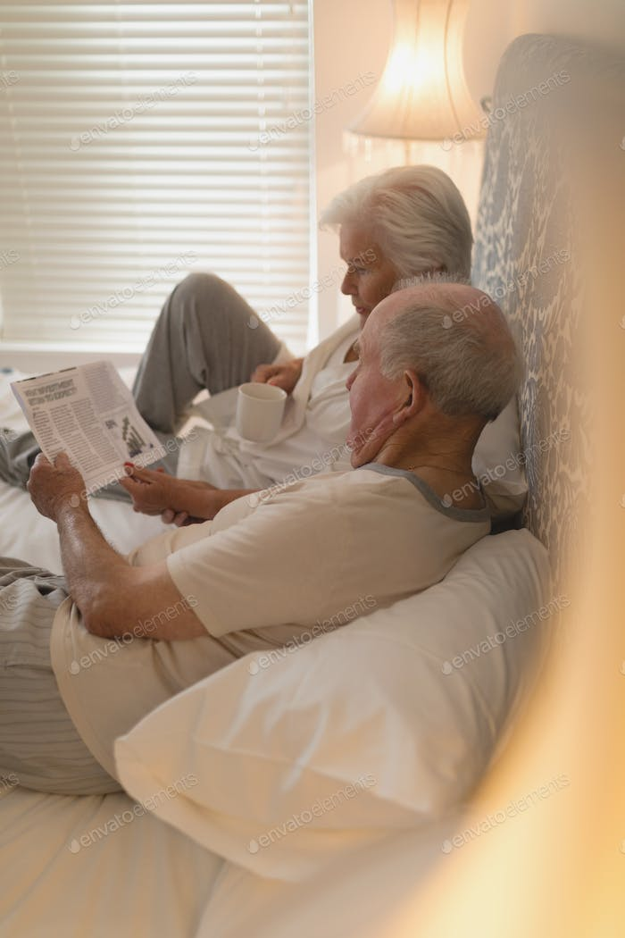 Side view of senior couple reading newspaper and drinking on the bed at home