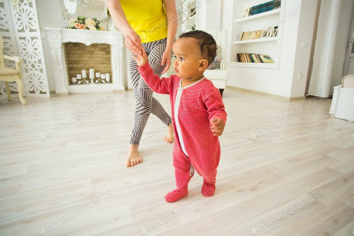 Cute little baby learning to walk, mom is holding his hands