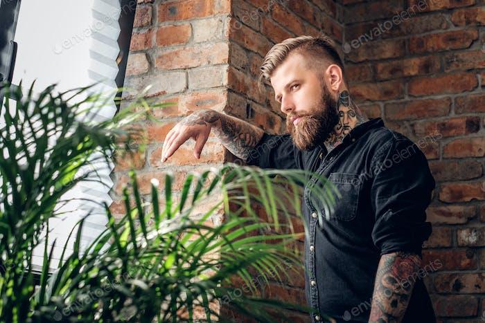 Portrait of bearded tattooed male in a room.