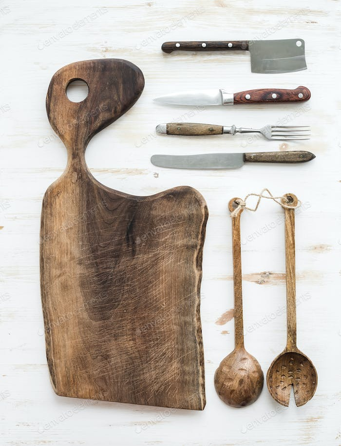 Kitchen-ware set. Old rustic chopping board made of walnut wood, knives, fork and salad spoons