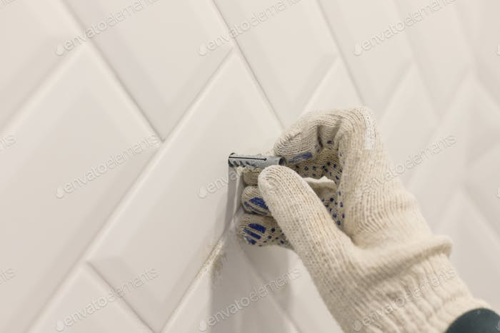 Worker's hand in glove inserts wall pvc dowel in wall cladded with tile ceramic