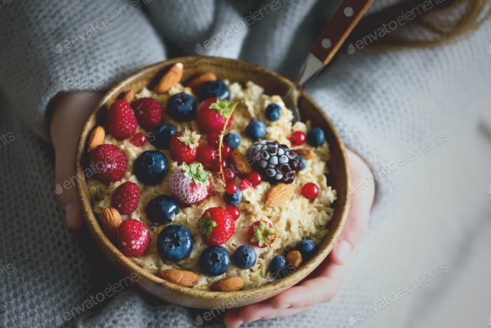 Mädchen Hände halten Haferflocken Brei mit gefrorenen Beeren, Mandeln in Holzschüssel. Gesundes Frühstück