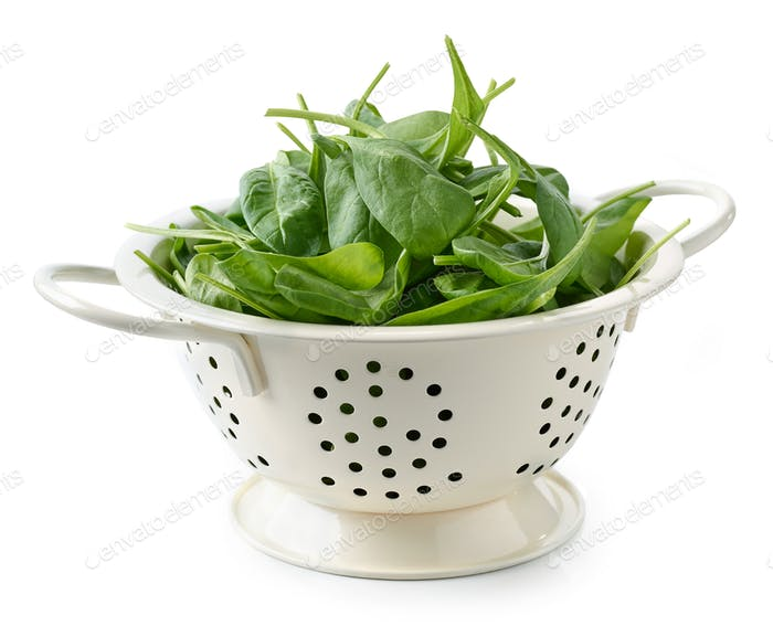 fresh spinach leaves in white colander