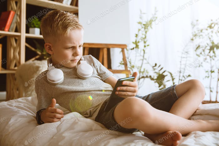 Little boy using different gadgets at home
