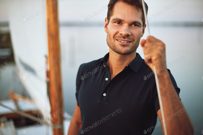 Young man smiling while sailing on his yacht deck