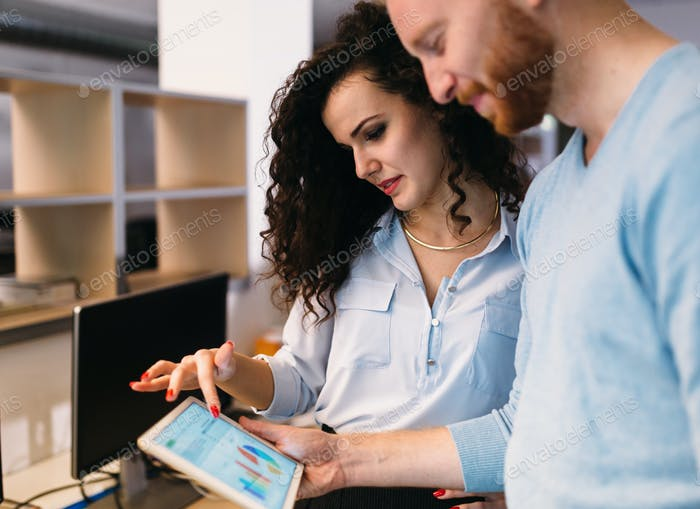 Software engineers using digital tablet in office