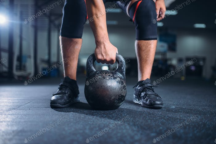 Male athlete prepares for exercise with kettlebell
