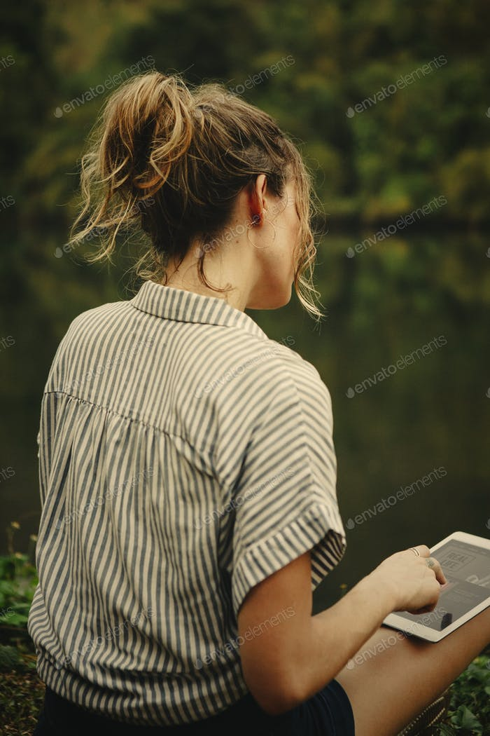 Woman alone in nature using a digital tablet with entertainment
