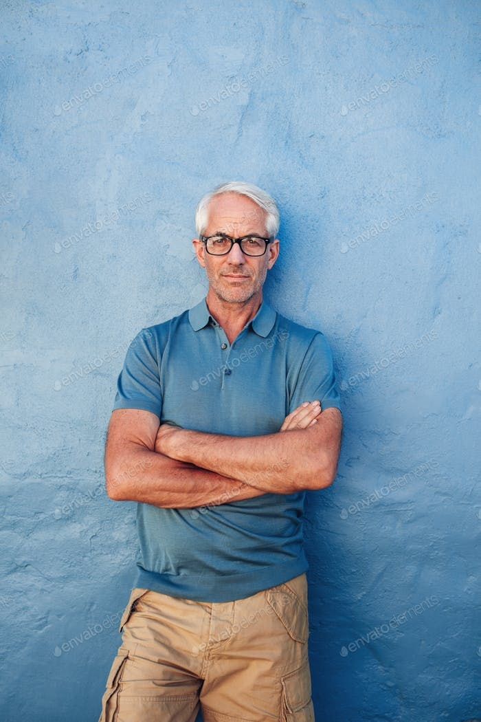 Confident mature man standing against a blue background